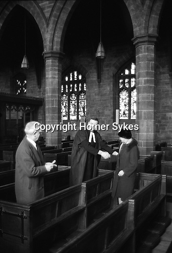 Henry Travice Charity, Maundy Thursday, St Mary the Virgin Church, Leigh Manchester, Lancashire England 1973.<br /> <br /> The Rev John Rogan MA, and one of his Church Wardens distribute the dole.<br /> <br /> On a pew west of the second pillar of the north arcade of the nave is a brass plate, marking the burial place of Henry Travice of Light Oakes, 1626, who founded a charity by which 5s. was to be given to forty poor people yearly on Thursday in Passion Week near his gravestone. Recipients have to walk the length of Henry Travice's pew, in 1973 ten people received a pound each.<br /> <br /> The Henry Travice Charity dole no longer takes place. Since 2013,  the money has been given to Atherton and Leigh Food Bank, helping to feed the poor.