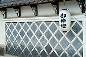 "An outer wall of a Japanese house done in the style of a castle. The lantern reads ""Goshinto"", meaning that this is a ""lantern for god"". Artists also have these for good luck."