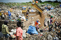 Taupik, 14, watching a truck deliver a load of dusty waste at the 'Trash mountain', Makassar, Sulawesi, Indonesia.