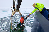 Technicians trying to locate an unmanned research vehicle somewhere under the slurry of ice in a pool that the ship's water jets were trying to keep open, Arctic Ocean.