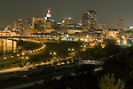 As trains pass below, the city of St. Paul, Minnesota glows in the night as seen from the Dayton's Bluff scenic overlook.