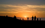 A couple embraces on the beach as the sunsets at Venice Beach, California
