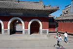Just outside the entrace of Miaoying Temple, also called the White Stupa Temple in Beijing ,China kids play tennis.