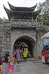 pedestrians pass street vendors as they head under the pagoda roofed stone wall that leads from the wharf to the town of Yangchou, along the River Li in China