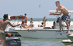 Two participants at the White Trash Bash at Dog Island off the coast of Carrabelle share a pair of sunglasses Sunday May 27, 2007.    (Mark Wallheiser/TallahasseeStock.com)