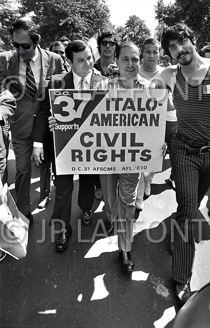 "Manhattan, New York City, New York State, USA. June 29th,1970. Joe Colombo, founder of the Italian American Civil Rights League and alleged organized crime boss, holds a sign as he walks among the crowd of 75,000 Italian Americans in the streets of New York during Italian Unity Day. His son Anthony (dark suit) walks next to him. The sign reads ""D.C. 37 Supports ITALO-AMERICAN CIVIL RIGHTS."""
