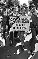 """Manhattan, New York City, New York State, USA. June 29th,1970. Joe Colombo, founder of the Italian American Civil Rights League and alleged organized crime boss, holds a sign as he walks among the crowd of 75,000 Italian Americans in the streets of New York during Italian Unity Day. His son Anthony (dark suit) walks next to him. The sign reads """"D.C. 37 Supports ITALO-AMERICAN CIVIL RIGHTS."""""""