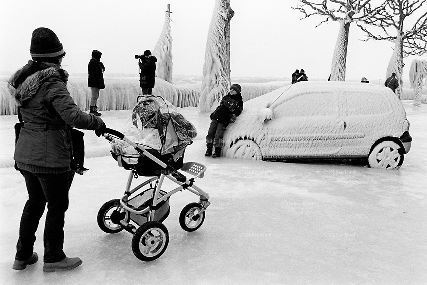 Switzerland. Canton Geneva. Versoix. Frozen car. The car has been parked close to the lake. The wind blew lake's water on the car which froze and is totaly stuck in the ice. Tourists take pictures. A mother with baby stroller. Versoix is distant 10 km from Geneva. 12.02.2012 © 2012 Didier Ruef