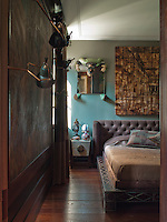 In the guest bedroom, black lacquer and bronze wall lighting highlights the Egyptian Art Deco panel