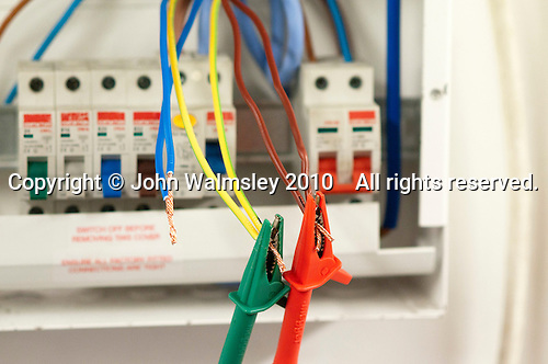 Student electrician attaches clips to test the wiring, Able Skills, Dartford, Kent.