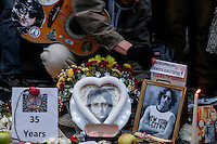 A Fan places a poster next to John Lennon picture around the 'Strawberry Fields'  in Central Park during the 35-year anniversary of his death in New York December 8, 2015. The death of John Lennon still reverberates as a defining moment for a generation and for the music world. Police said the shooting occurred outside the Dakota, the century-old luxury apartment house where Lennon and his wife, Yoko Ono, lived. It is across the street from Central Park. Kena Betancur/VIEWpress.