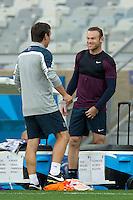 Wayne Rooney of England jokes with coach Gary Neville during training