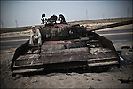 © Remi OCHLIK/IP3 -  Benghazi March 25, 2011 - A rebel fighter rest on a destryed tank hit by French war jets.