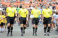 MLS referee Mark Geiger holding the ball with assistants coming into the field. D.C. United tied The Philadelphia Union 1-1 at RFK Stadium, Saturday August 19, 2012.