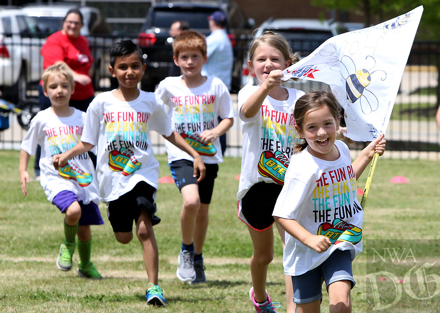 NWA Democrat-Gazette/DAVID GOTTSCHALK  Kaylee Moore (from right) and Addy Gosselin, first grade students at Butterfield Trail Elementary School, run with their class flag and classmates during opening activities of the Boosterthon Fun Run at the school in Fayetteville. Kindergarten through fourth grade students participated in the interactive character program sponsored by the Parent Teacher Organizaion and presented by Boosterthon to raise funds for an indoor climbing wall and playground sports field at the school.