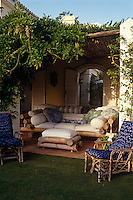 A comfortable bamboo sofa piled high with an assortment of scatter cushions and a matching footstool on a covered terrace