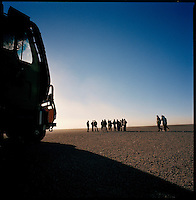 Djebel Al Weinat, deep Sahara desert, Libya, December 2004..Every week, a convoy of 40 privately owned Libyan trucks loaded by the WFP with about 1000 metric tons of western food aid cross 2500 km of deep desert across Libya and Chad to reach more than 200 000 refugees from Darfur in camps near the Sudanese border. The convoy assembles in the morning under the protection of the Libyan army.