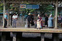 Amish family awaits train at Lancaster, PA railroad station.