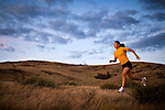 A woman runs on a grassy hillside at dusk.