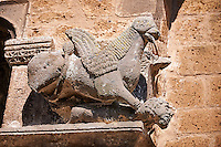 Griffin holding a decaptiated mans head on the faceade of the Basilica Church of Santa Maria Maggiore, Tuscania