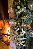 Close up of a spruce and fern Christmas arrangement around the fireplace decorated with glass baubles