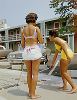 Cavalier Motel, Bass River, MA. Two young girls in bathing suits playing shuffleboard