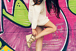 Headless shot of a woman with long brown hair and a baggy white shirt, fixing the strap of her sandal with colorful graffiti on the background.