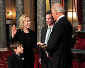 United States Senator Kirsten Gillibrand (Democrat of New York), left center, raises her right hand during the photo-op of the reenactment of her swearing-in in the Old Senate Chamber in the U.S. Capitol in Washington, D.C. on Wednesday, January 5, 2011.  U.S. Vice President Joe Biden, right, administers the oath.  Looking on is son Theo, left, and husband Jonathan, center right..Credit: Ron Sachs / CNP.(RESTRICTION: NO New York or New Jersey Newspapers or newspapers within a 75 mile radius of New York City)