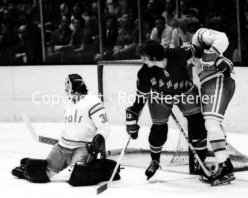 Seals vs New York Rangers 1974. Bob Stewart holds off Ranger Jerry Butler from his goalie Ted Tucker.<br />(photo/Ron Riesterer)