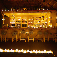 The rustic bar of the Hotelito Desconocido with its hand-painted wooden counter is candlelit at night