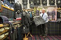 Il proprietario del negozio mostra dei tessuti tartan  The owner of the shop with the different tartan tissues