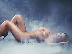 Beautiful nude young woman lying down surrounded with smoke