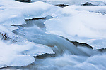 Ice and snow along Kootenai Creek in winter in as it flows out of the Bitterroot Mountains in western Montana