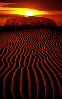 Sun over Ayers Rock, with red Sand Dunes
