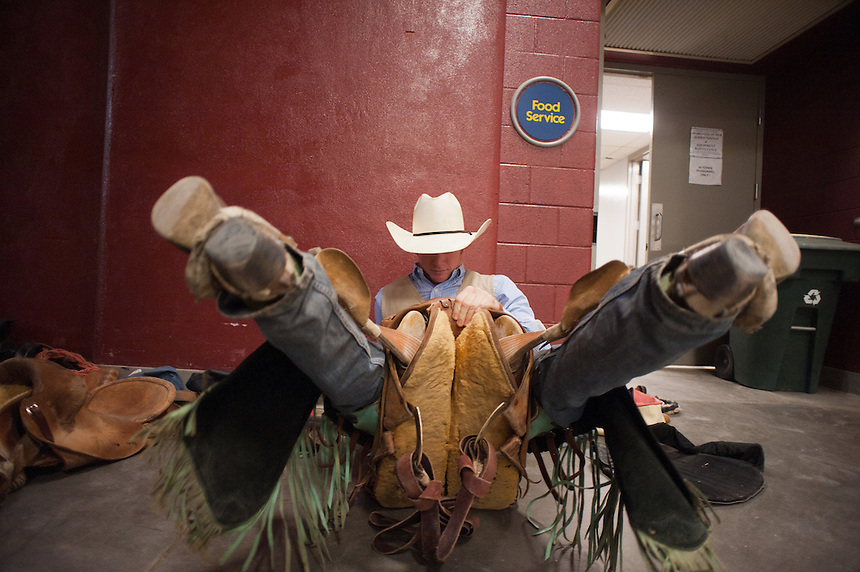 Saddle bronc rider Jacobs (cq) Crawley warms up in his saddle in a hallway at the College National Finals Rodeo in Casper, Wyo., Saturday, June 18, 2011. Unlike college athletes in other sports, student rodeo atheletes are allowed to compete for money and sign with sponsors. (Kevin Moloney for the New York Times)