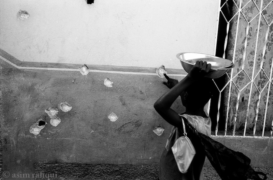 a girl walks past a house riddled with bullet holes made when MINUSTAH armored personnel carriers fired into densly populated neighborhoods.  the extent of civilian casualties and property damage in cite soleil as a result of MINUSTAH operations against 'armed gunmen' remains poorly documented and mostly unreported<br />