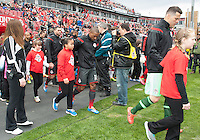 Toronto, Ontario - May 3, 2014: Toronto FC forward Jermain Defoe #18 walls onto the pitch with a player escort during the opening ceremonies in a game between the New England Revolution and Toronto FC at BMO Field.<br /> The New England Revolution won 2-1.