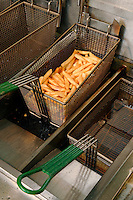 Potato chips/french fries coming out of cooking oil.<br />