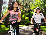 Two happy smiling children enjoying bicycle ride in a park, brother and sister, 10 and 13. Active outdoor summer lifestyle.