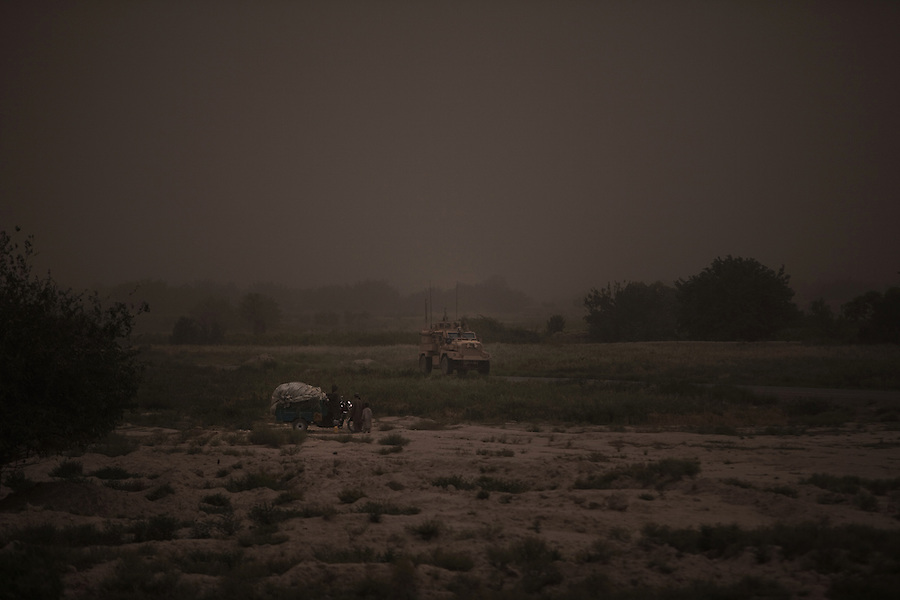 An Army MRAP and Afghan motor bike cross paths in the dust near Combat Outpost Fitzpatrick in Zhari District, Kandahar, Afghanistan. The violently contested district sits astride the strategically Highway 1 ringroad between Kandahar and Lashkar Gah and is seen by some as the birthplace of the Taliban movement.
