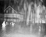 This dramatic rescue occurred at the height of the storm at Riverside and Summit Streets. Deputy Fire Chief Frank Moore, white coat and waist-deep in flood water, and Battalion Chief Walter Joy, directly ahead of him, direct rescue operation of three stranded Waterbury firemen. Private William O'Neill, on the fence post, guides Private George Brown from the pole across the raging current. The House on the left was later swept away.