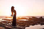 Beautiful woman by the sea at sunset.