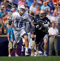 Justin Turri (12) of Duke tries to find a path past Quinn Cully (41) of Notre Dame during the NCAA Men's Lacrosse Championship held at M&T Stadium in Baltimore, MD.  Duke defeated Notre Dame, 6-5, to win the title in overtime.