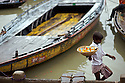 A young boy makes his way past wooden boats on a rainy morning on his way towards pilgrims visiting the banks of the Ganges River, Varanasi, India.