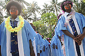 "Students in gowns and decorative face paint wait for graduation ceremonies to begin at their end of academic year ""school closing"", on Han Island, Carterets Atoll, Papua New Guinea, on Monday, Dec. 11, 2006.  Rising sea levels have eroded much of the coastlines of the low lying Carteret islands (situated 80km from Bougainville island, in the South Pacific), and waves have crashed over the islands flooding and destroying what little crop gardens the islanders have. Food is in short supply, banana and swamp taro crops are failing due to the salt contamination of the land, and the islanders live on a meagre one meal per day diet of fish and coconut. There is talk by the Autonomous Region of Bougainville government to relocate the Carteret Islanders to Bougainville island, but this plan is stalled due to a lack of finances, resources, land and coordination."