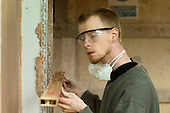 Plastering student with a spirit level, Able Skills, Dartford, Kent.