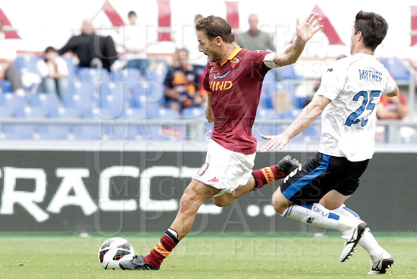 Calcio, Serie A: Roma vs Atalanta. Roma, stadio Olimpico, 7 ottobre 2012..AS Roma forward Francesco Totti kicks the ball as Atalanta defender Carlos Javier Matheu, of Argentina, right, challenges him during the Italian Serie A football match between AS Roma and Atalanta at Rome's Olympic stadium, 7 october 2012..UPDATE IMAGES PRESS/Riccardo De Luca