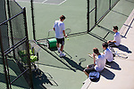 Players sit on the sidelines as Pinewood School tennis players participate in a match.