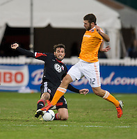 Emiliano Dudar (19) of D.C. United tackles the ball away from Will Bruin (12) of Houston Dynamo during the game at RFK Stadium in Washington,DC. D.C. United tied the Houston Dynamo, 1-1.  With the tie, Houston won the Eastern Conference and advanced to the MLS Cup.