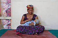 Amrita Rokya, 18, cradles her 2-day-old baby in the Bardia District Hospital, one hour's walk from her village in Bardia, Western Nepal, on 29th June 2012. In Bardia, StC works with the district health office to build the capacity of female community health workers who are on the frontline of health service provision like ante-natal and post-natal care, and working together against child marriage and teenage pregnancy especially in rural areas. Photo by Suzanne Lee for Save The Children UK